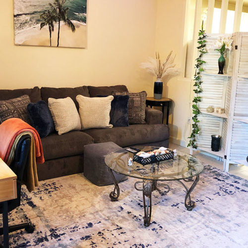 Living room furnished with sofa, coffee table and decor.